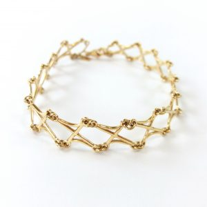 Gold bracelet on white background
