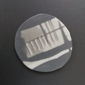 One white and grey parian porcelain coaster on grey background