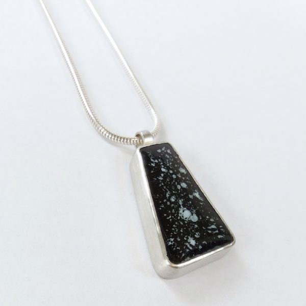 Silver pendant set with black tile on white background