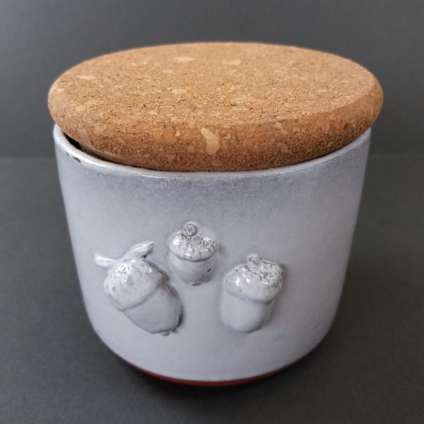 White ceramic pot with acorn design and cork lid on grey background