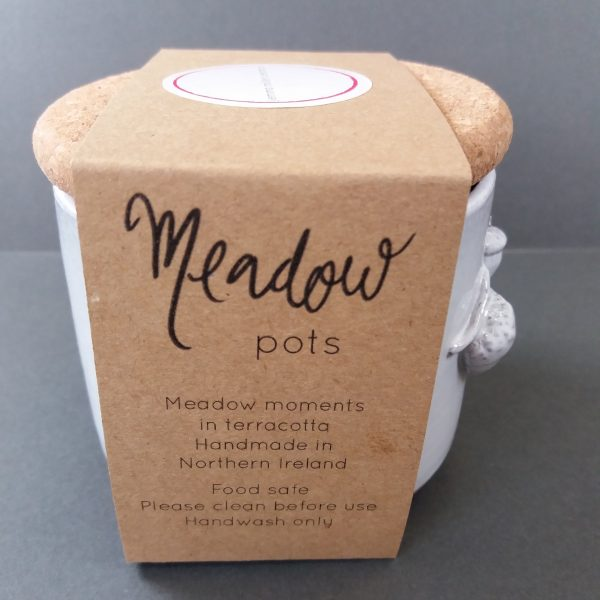 Side view of cardboard packaging of white ceramic meadow pot