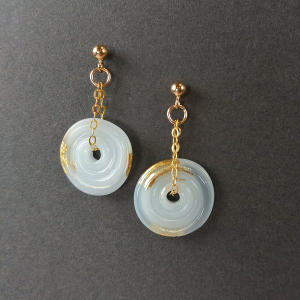 Pale blue disc earrings with gold fittings on grey background