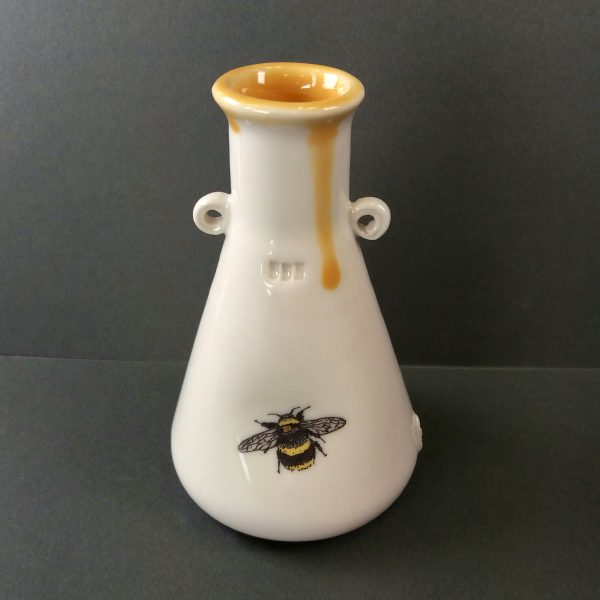 Porcelain bottle with bee decal on grey background