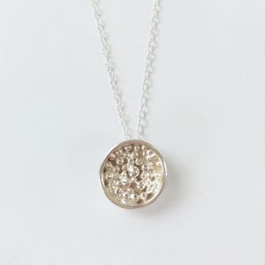 Round silver pendant with granulated details inside on silver chain