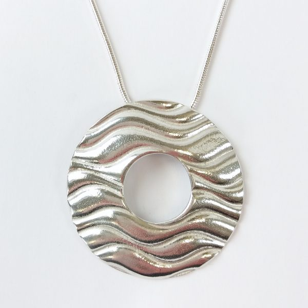 Round pewter pendant with hole in centre on chain