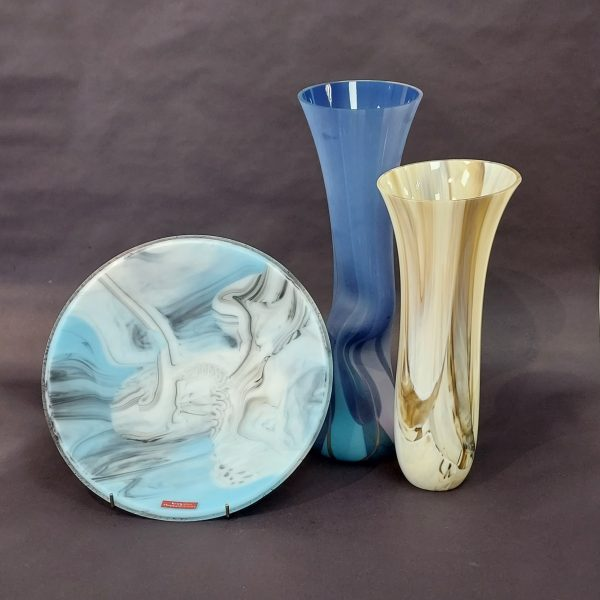Round blue glass plate beside a tall glass blue vase and cream brown vase against dark grey background