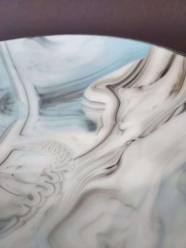 Detail of patter on glass plate white, blue black, grey swirls