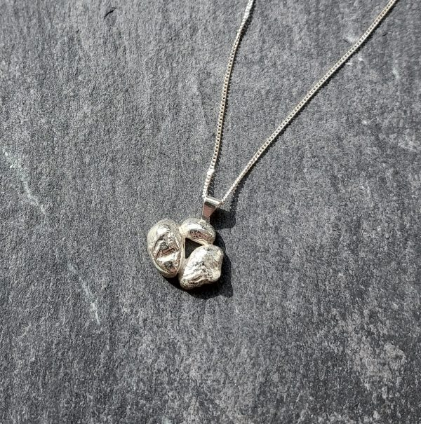 textured silver necklace on slate background