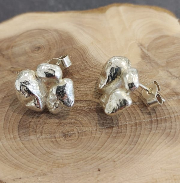 textured silver stud earrings on wooden display