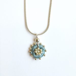 Round pale blue embroidered necklace on silver chain