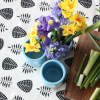 Leaf pattern table runner with flower vase and flowers and chopping board with cut spring onions