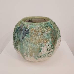 Earthenware round jar with various green glazes