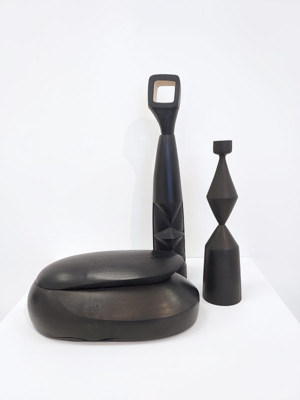 Collection of ebonised ash sculpture, candle stick and box