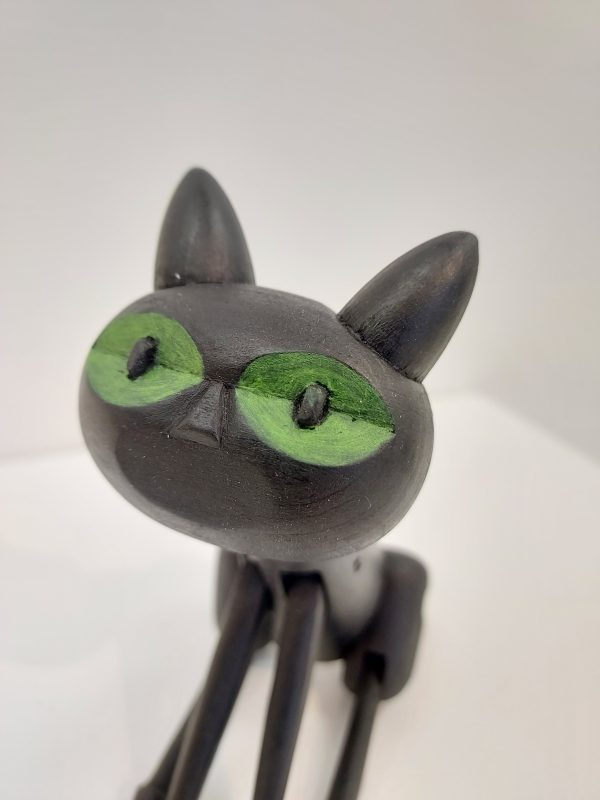 Detail of green eyes on black wooden toy cat