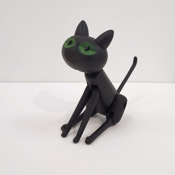 Handmade black wooden toy cat sitting
